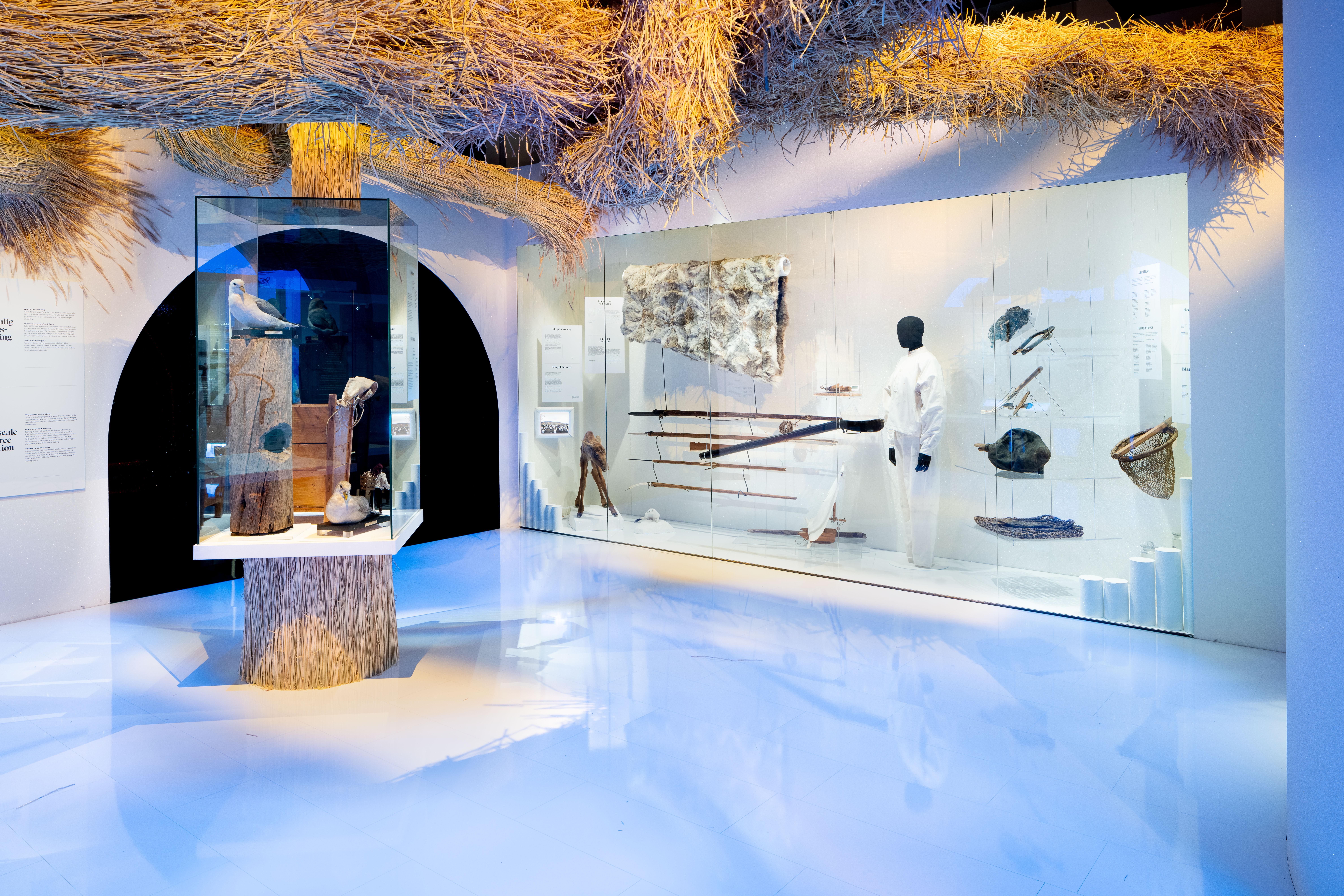 Vy över ett av utställningens rum. En monter på golvet med några föremål i, en monter i väggen med en jaktdräkt, vapen och vargfäll. Skulpturer av halm formade som rör hänger i taket.