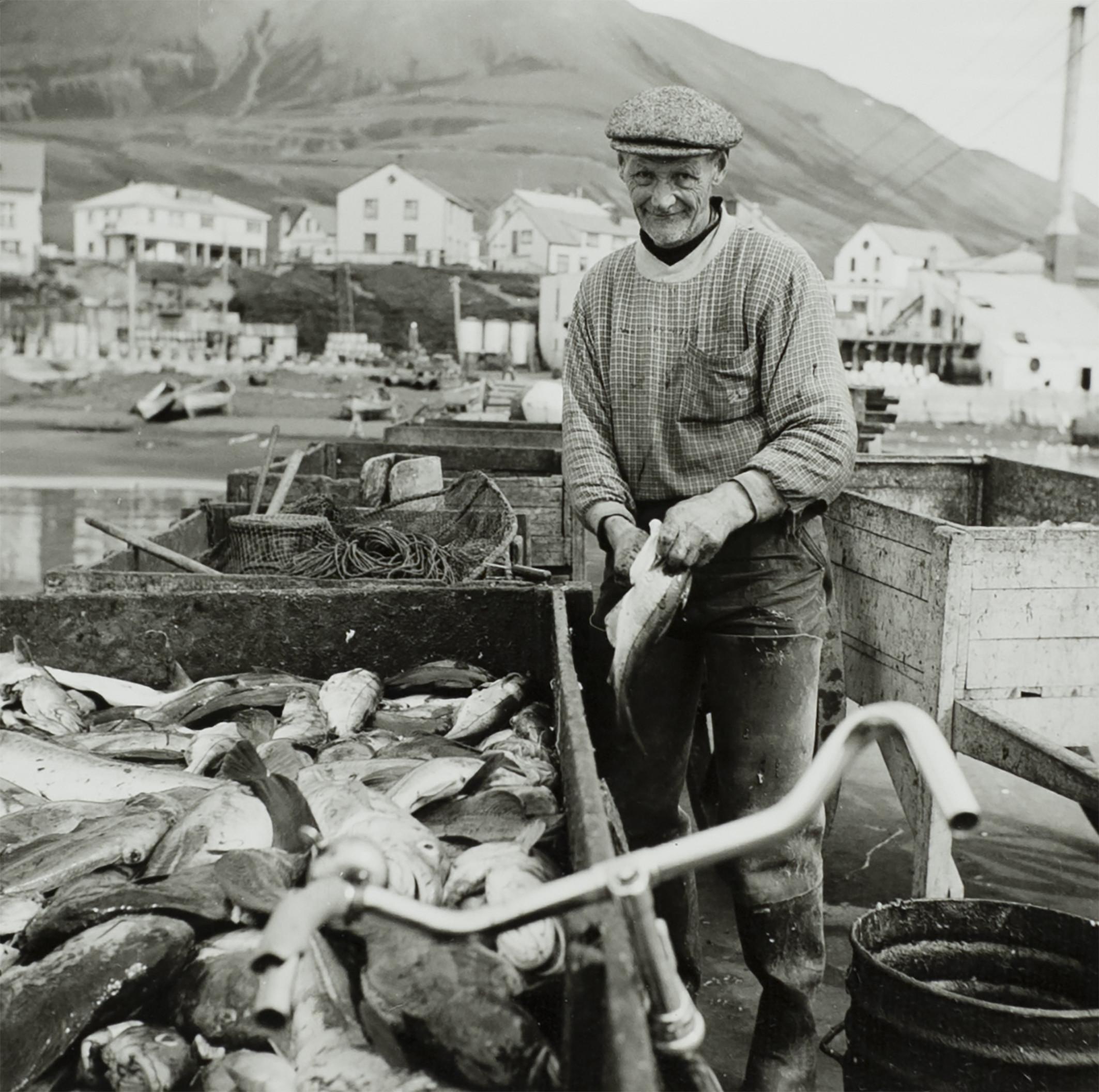 Svartvit bild av fiskare på Island. Står vid en stor behållare full med fisk och har en av fiskarna i händerna. Cykelstyre syns i förgrunden, i bakgrunden syns fler träbehållare med nät i, samt flera hus på andra sidan vattnet.