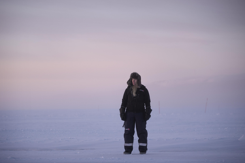 Kvinna i varma kläder och pälsmössa, på snötäckt is.