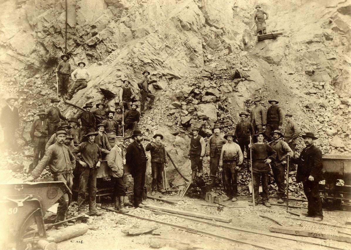 Bild över personalen i Kirunagruvan år 1911, som står uppställda mot bergväggen.