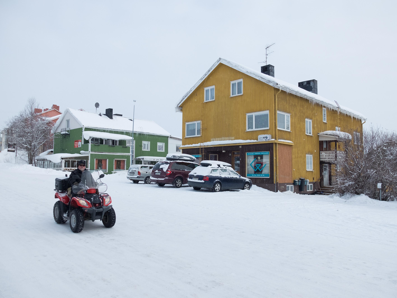 Man på fyrhjuling på snötäckt gata i staden Vilhelmina. Ett grönt och gult hus med snötäckta bilar syns vid gatukanten.