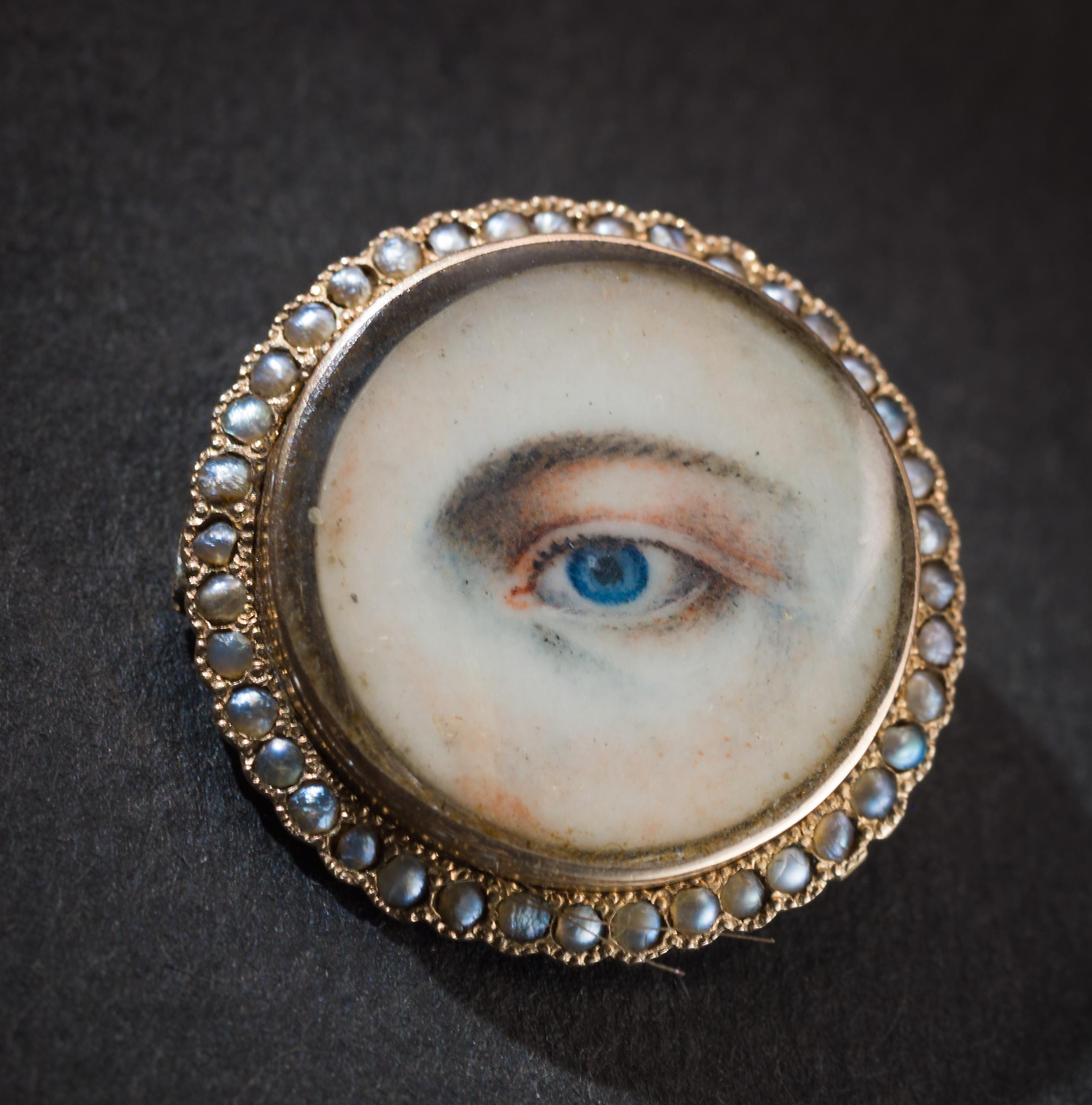 Brosch med hårslinga på baksidan Brosch av guld, ben, pärlor och hår från 1800-talets första hälft. Under den tunna benplattan med det målade ögat ligger en hårlock