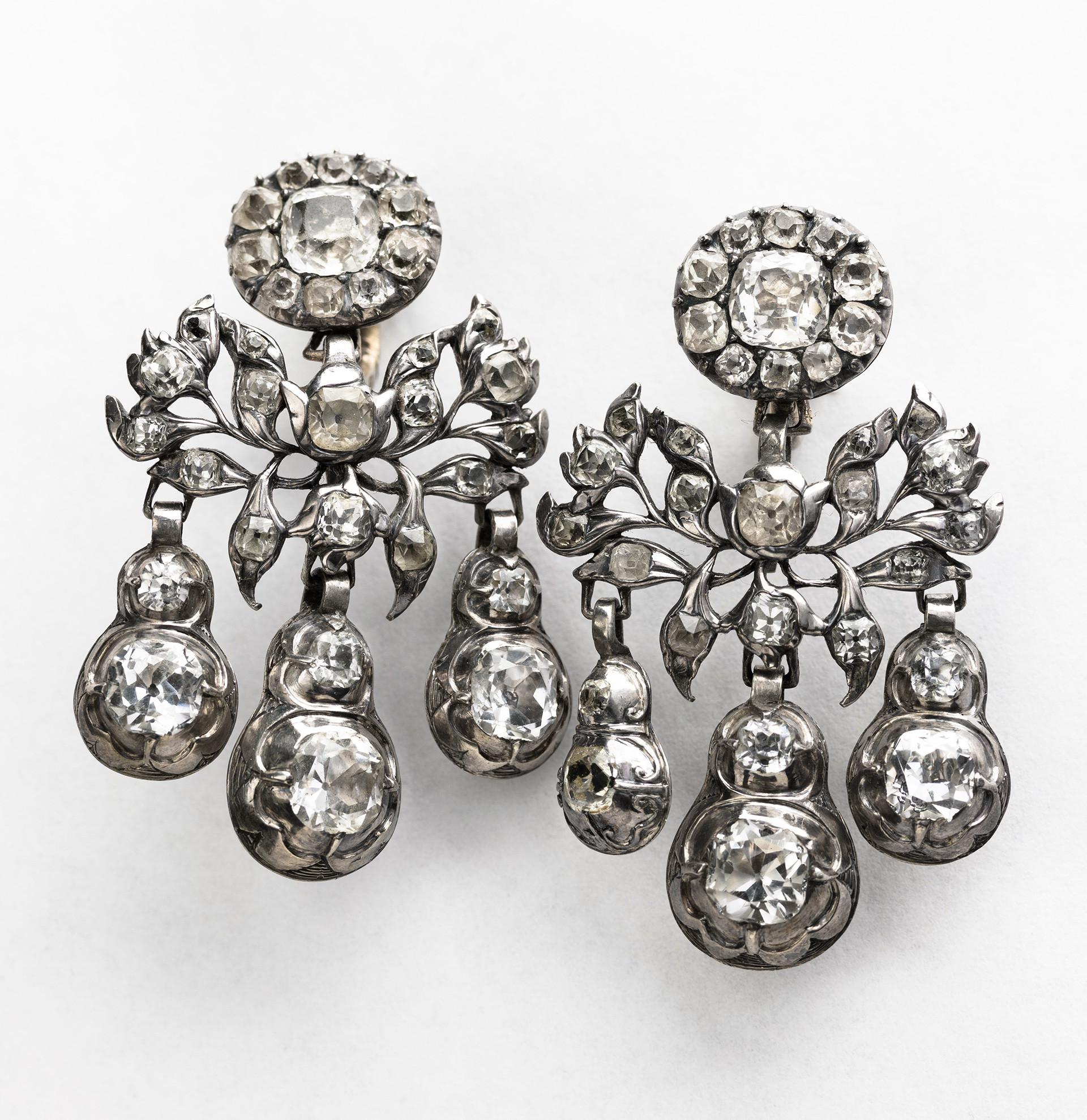 """Girandoler/örhängen. Örhängen och broscher med en rosettformation överst, därunder bladverk och slutligen tre hängande kläppar, kallas """"girandoler"""". Ordet kommer från franskan och betyder kandelaber, en stor ljusstake. Diamanter, fasettslipade bergkristaller eller glasstenar blev några av de mest omtyckta smyckestenarna under rokokotiden. Girandolerna på bilden är av silver och bergkristall, från 1700-talets mitt."""