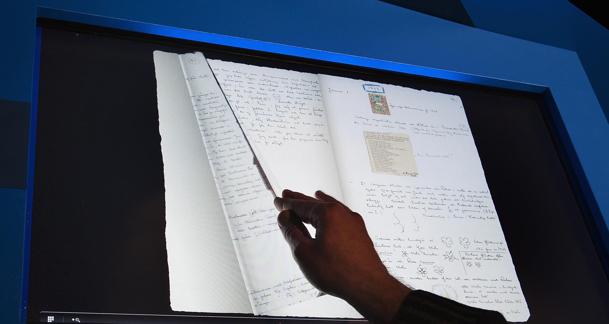 Hand som bläddrar i den digitala kopian av Ockulta Dagboken.