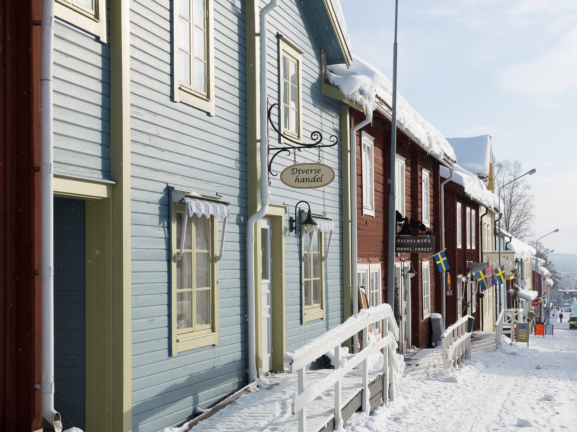Snötäckt gata med färgglada trähus i Vilhelmina. Foto: Nordiska museet
