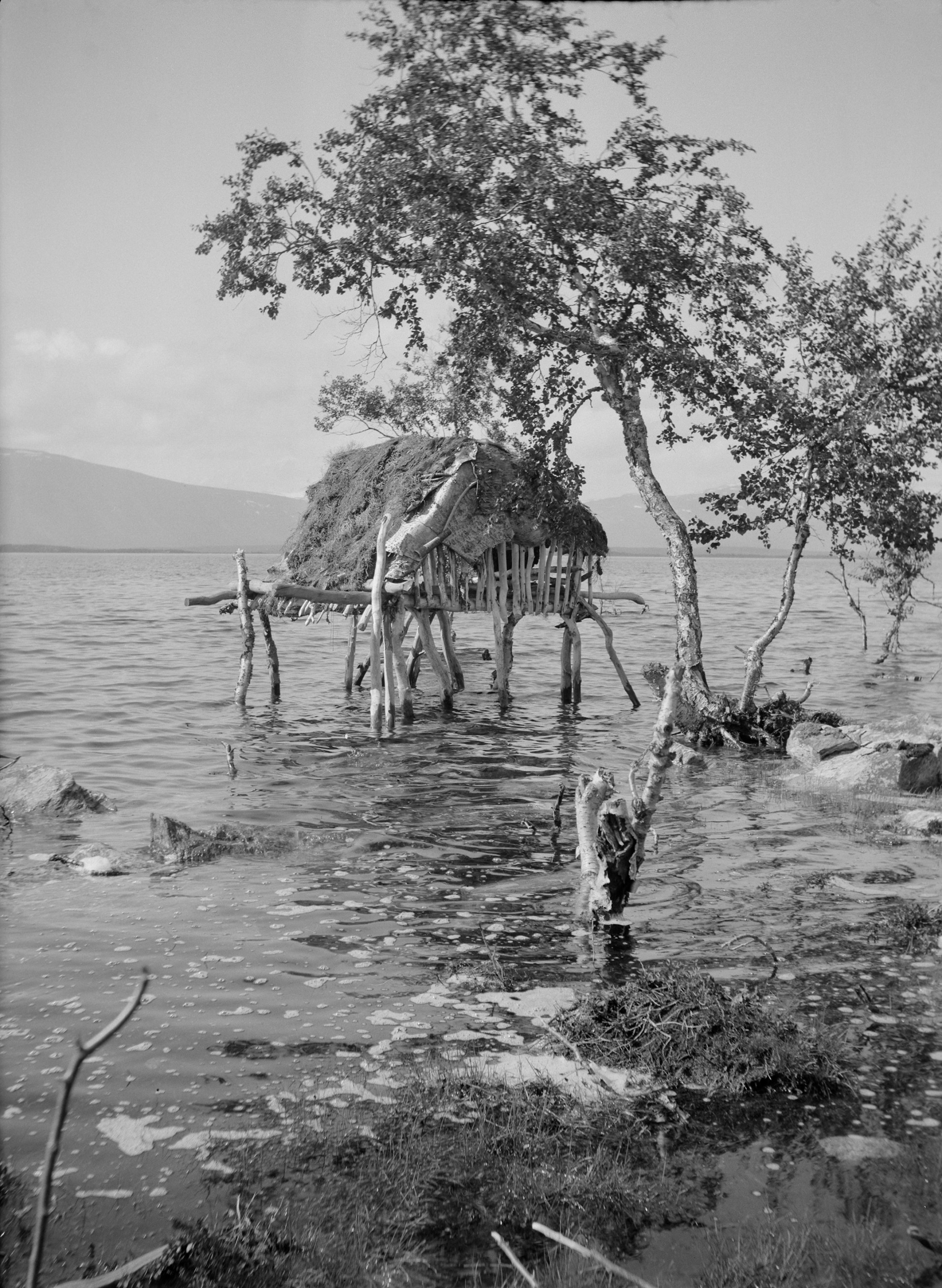 Flooded hut site with a luovve (storage hut) still standing, Ritsemjokk, Sörkaitums herding cooperative. 1939. Photo: Ernst Manker/Nordiska museet