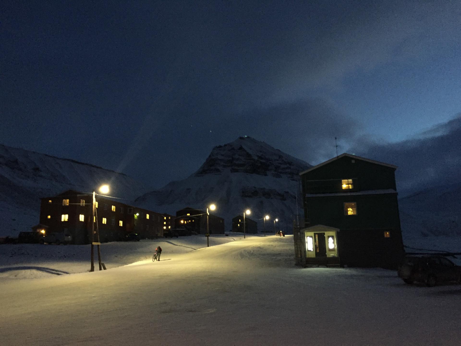 Mörk väg på Svalbard, Norge. En person syns gå med sin cykel under gatlyktornas gula sken.