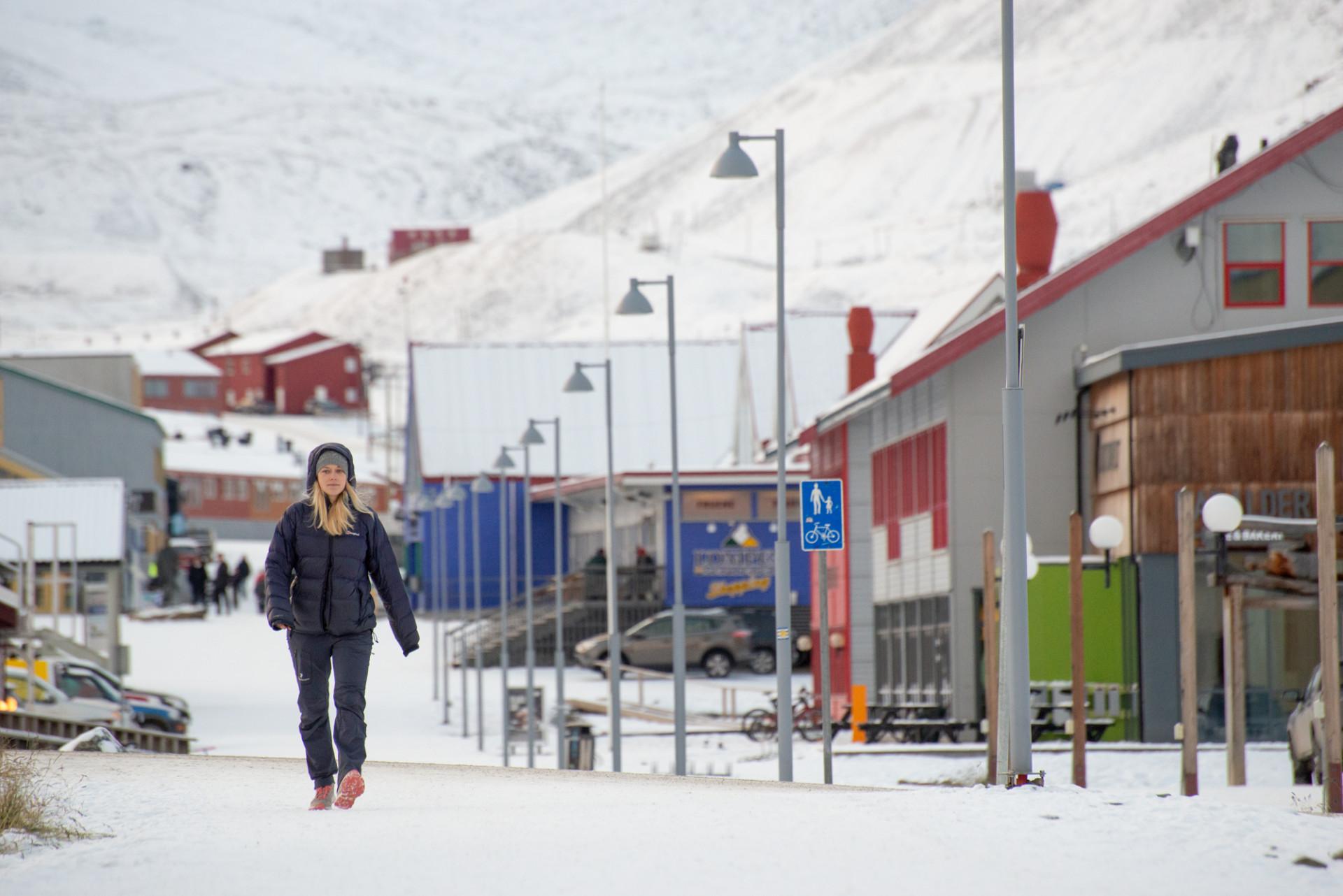 Kvinna som promenerar på en vintrig gata i Longyearbyen, Svalbard