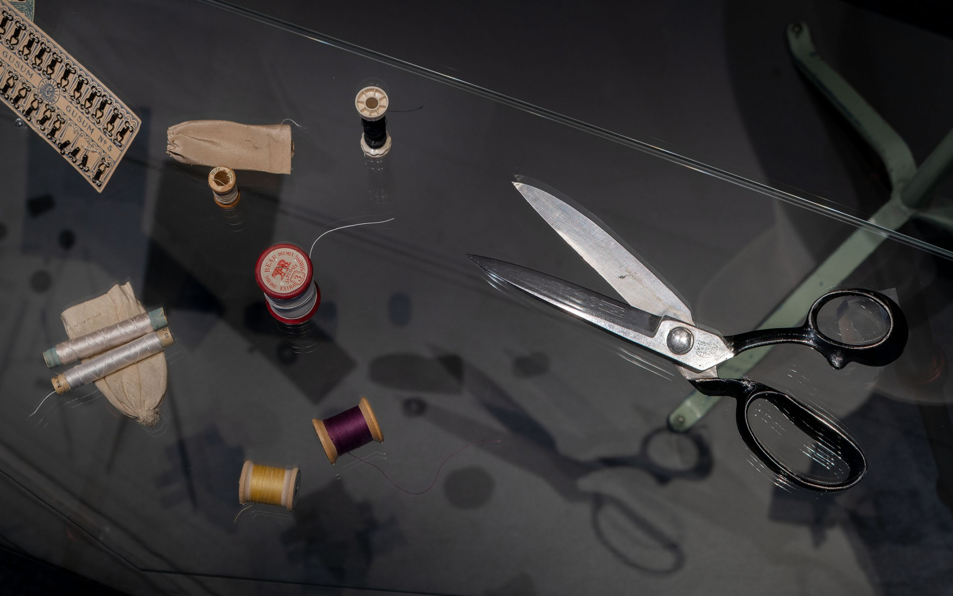 Sax, trådrullar och andra föremål från en syateljé i en monter
