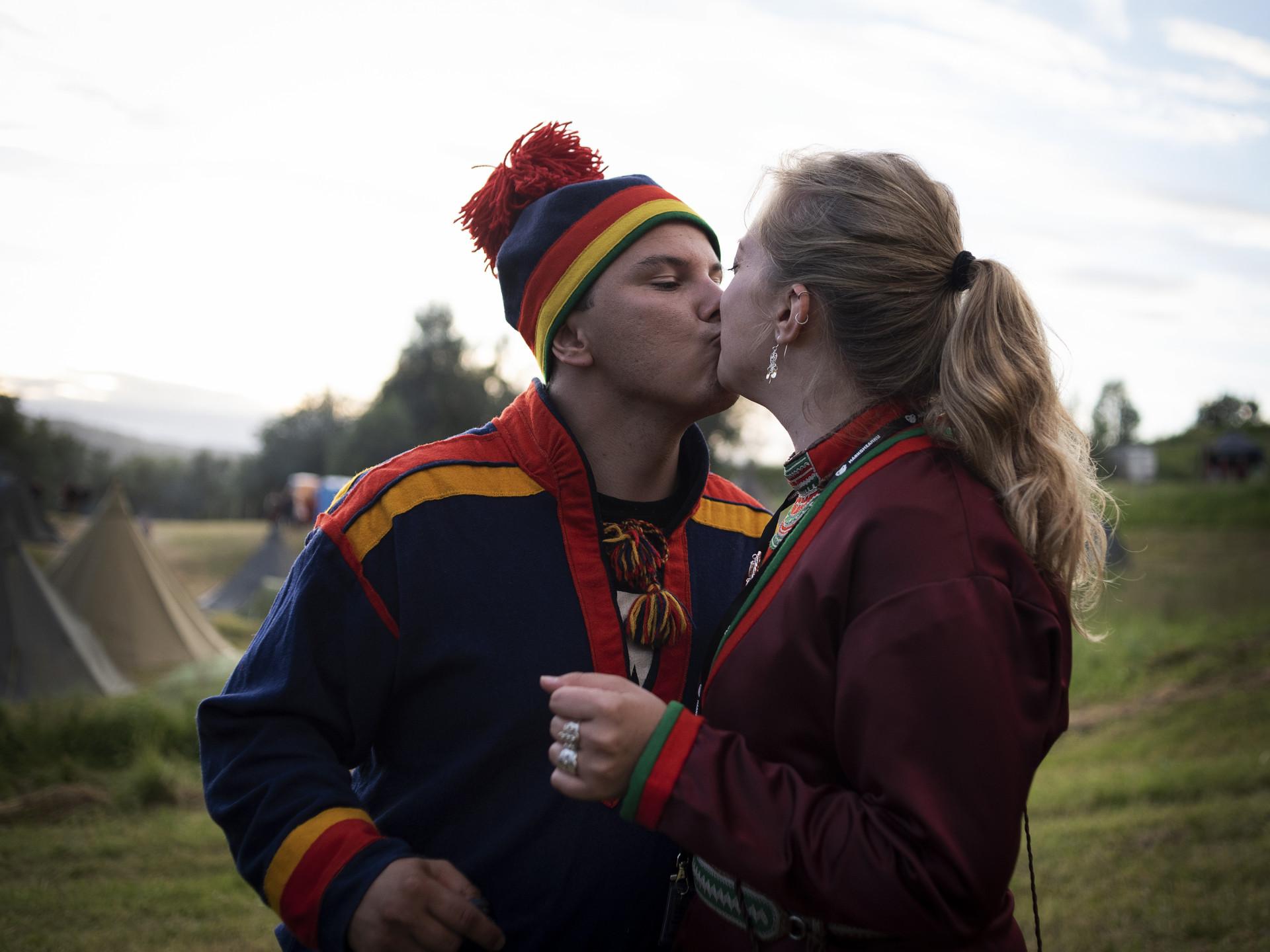 Kille och tjej som pussas på Markumeannu festival, Norge. I traditionella samiska kläder.