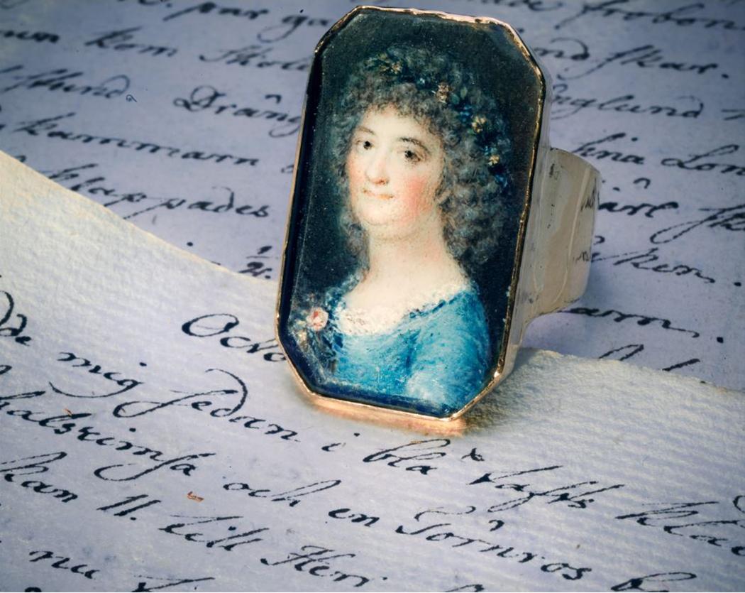 Årstafruns ring. Att få sitt porträtt målat var en speciell händelse under det sena 1700-talet. Årstafrun, Märta Helena Reenstierna (1753-1841) hade både ny frisyr och en stor dos tålamod när hon poserade i sammanlagt femton timmar för detta porträtt år 1796. Ringen var en namnsdagspresent till maken, Christian Henrik von Schnell den 13 november 1796. Bilden är det hittills enda kända porträttet av Årstafrun. Porträttet är målat på ben av marinofficeren och miniatyrmålaren Jacob Henric Röngren. Infattningen
