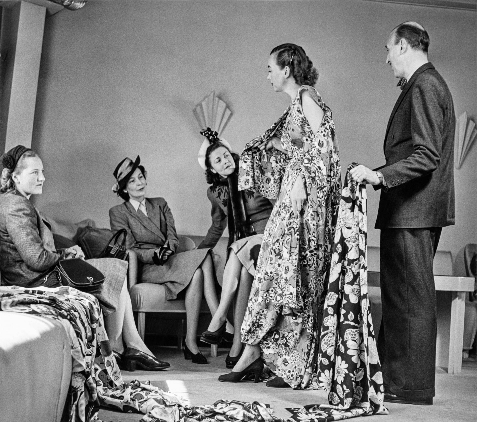 tre kunder en mannekäng och en designer tittar på tyger och klänning