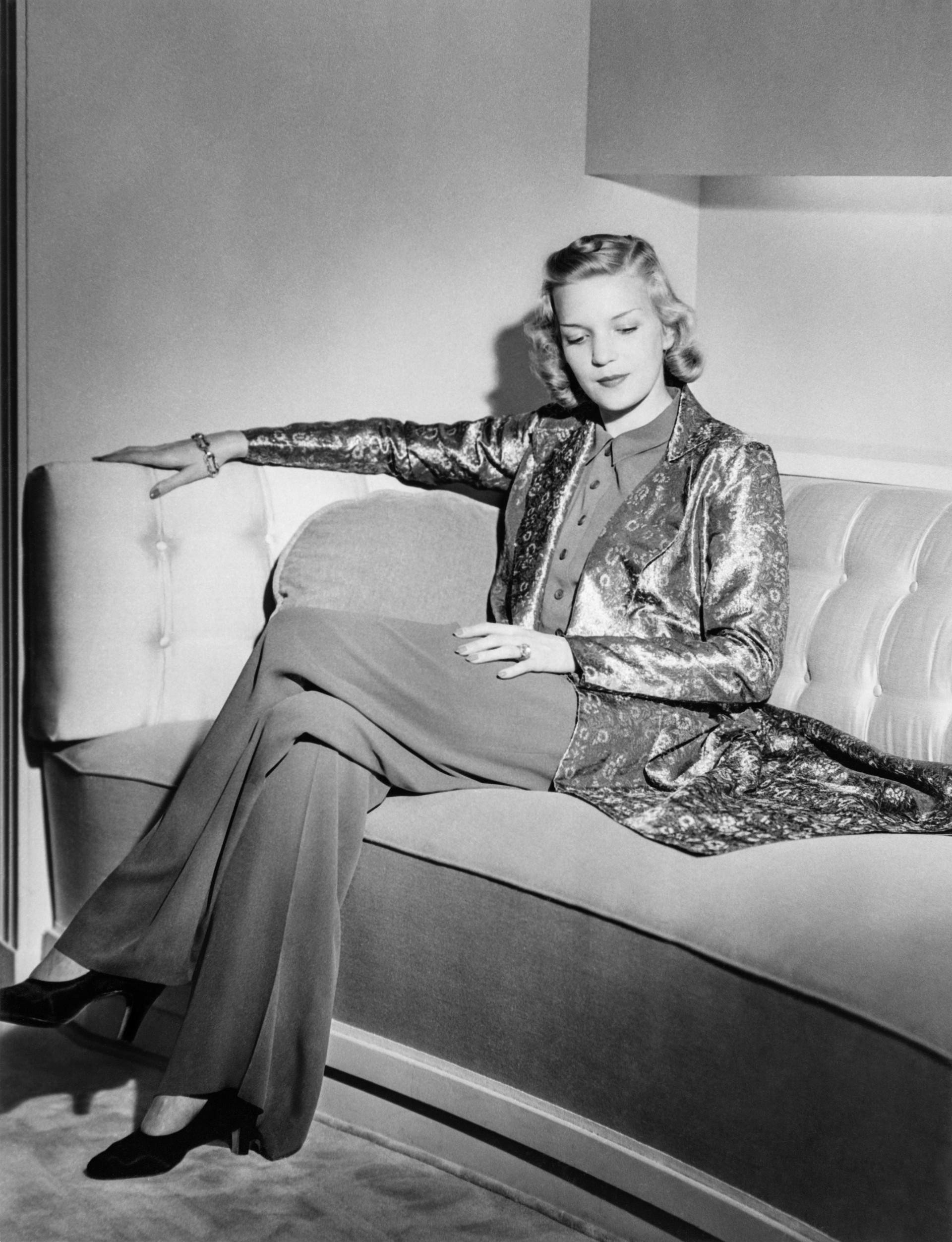 En mannekäng i långbyxa och lång kavaj sitter i en soffa