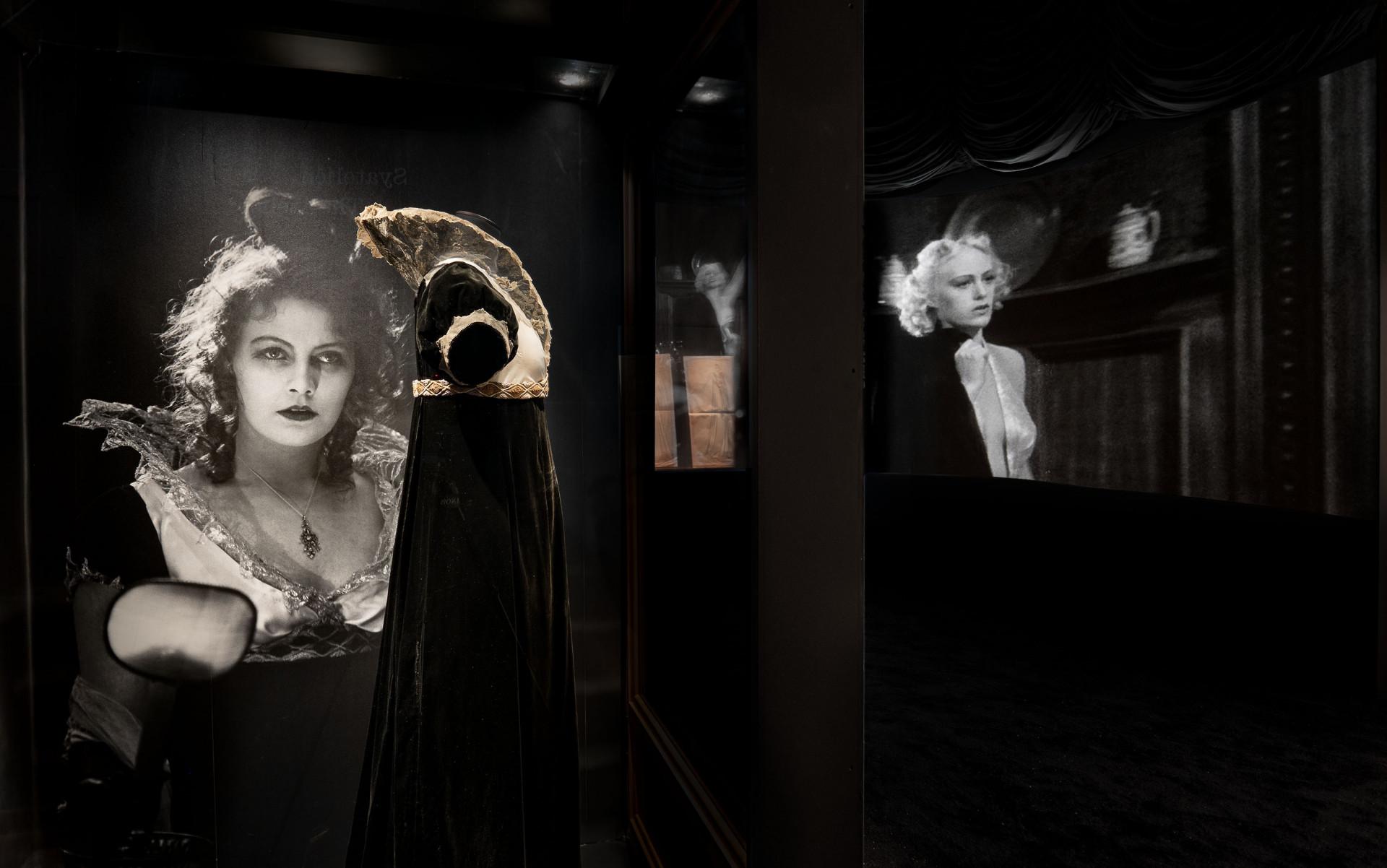 ett mörkt utställningsrum med en bild av Greta Garbo, en svart klänning och två filmdukar med svartvit film
