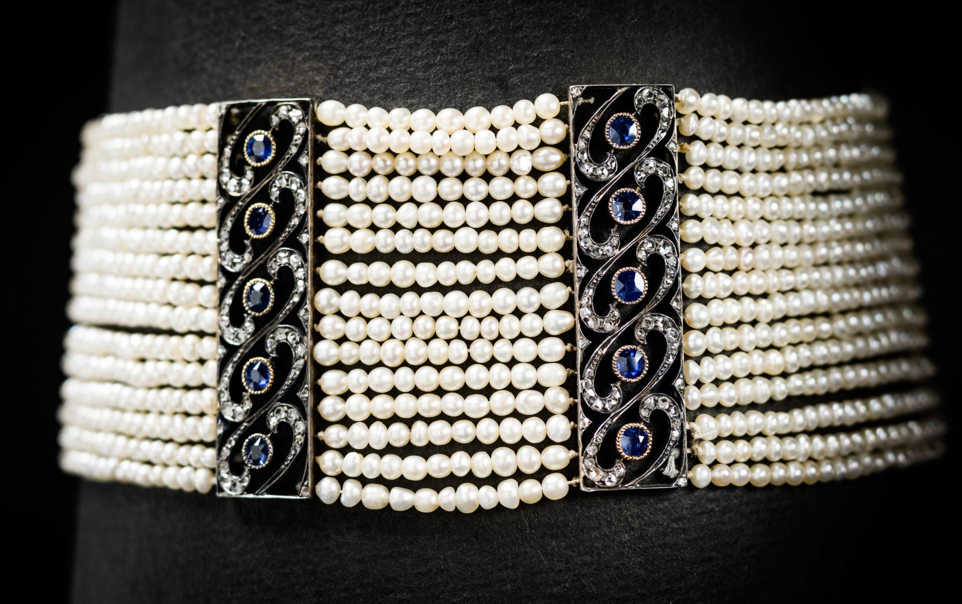 """Denna typ av halsband kallas i England dog collar och i Frankrike collier de chien, vilket betyder """"hundhalsband"""". De ska sitta tätt runt halsen. Halsbanden var moderna inom högre samhällsskikt årtiondena kring sekelskiftet 1900. Halsbandet består av 1650 orientaliska pärlor uppträdda i femton rader, avdelade av vertikala stavar av vitt guld, besatta med safirer och diamanter. Foto: Mats Landin/ Nordiska museet."""