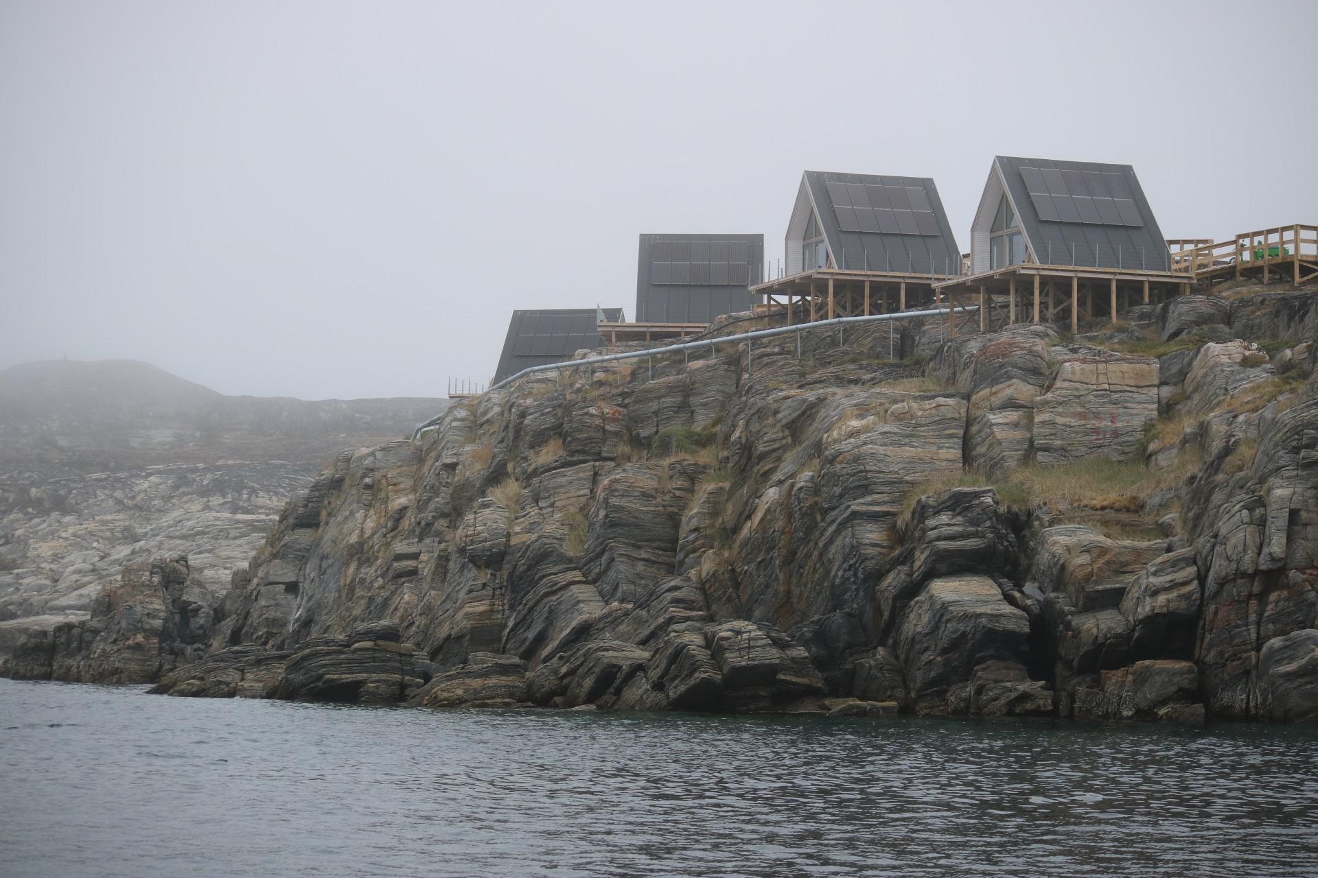 Hus på pålar på dimmiga klippor i Grönland. Foto: Nordiska museet