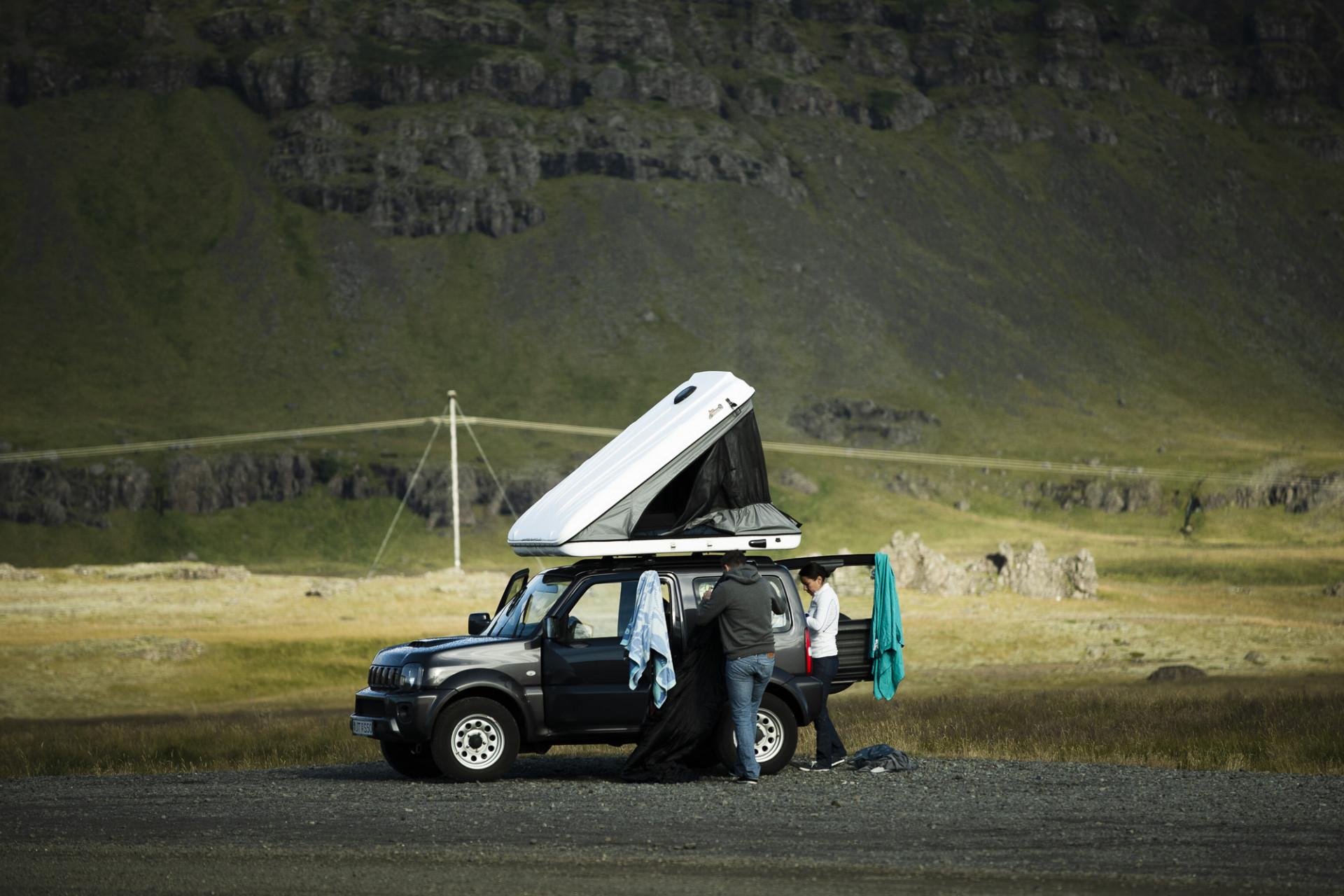 Jeep med stor takbox i naturen. Två personer sitter i bilen, kläder hänger ned från taket. Från Vatnajökull, Island.