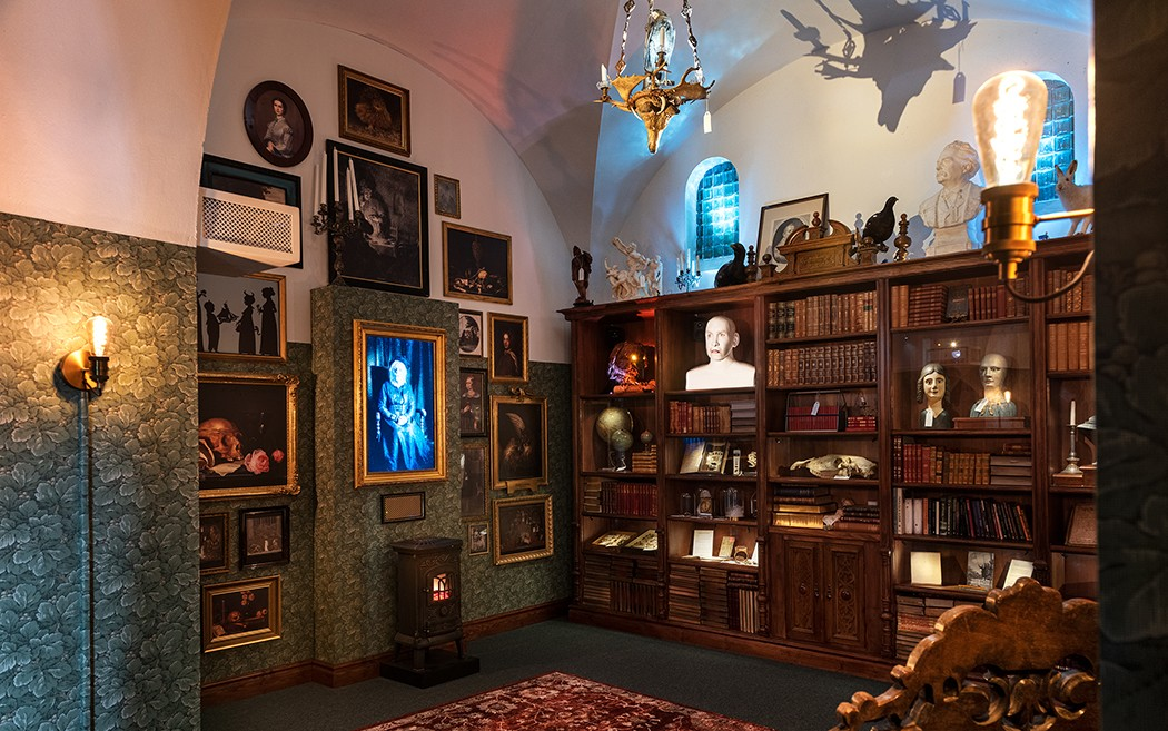 """ett rum som ser ut som ett gammalt bibliotek. En tavla och en gpisbyst i hyllan verkar """"leva""""."""
