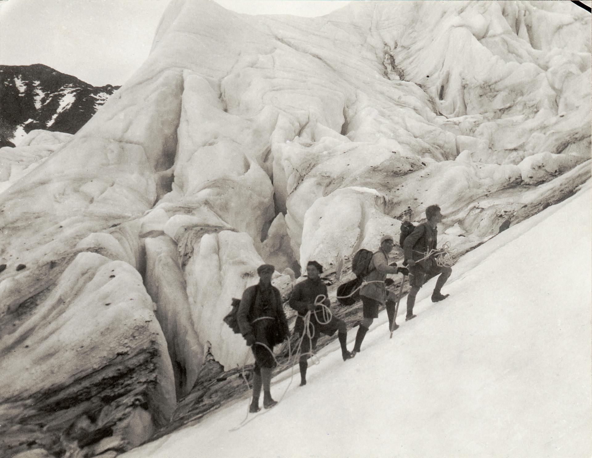Bergsklättrare på rad i snöigt landskap, sammankopplade med rep. Bestigning av Kebnekaise. Tidigt 1900-tal.