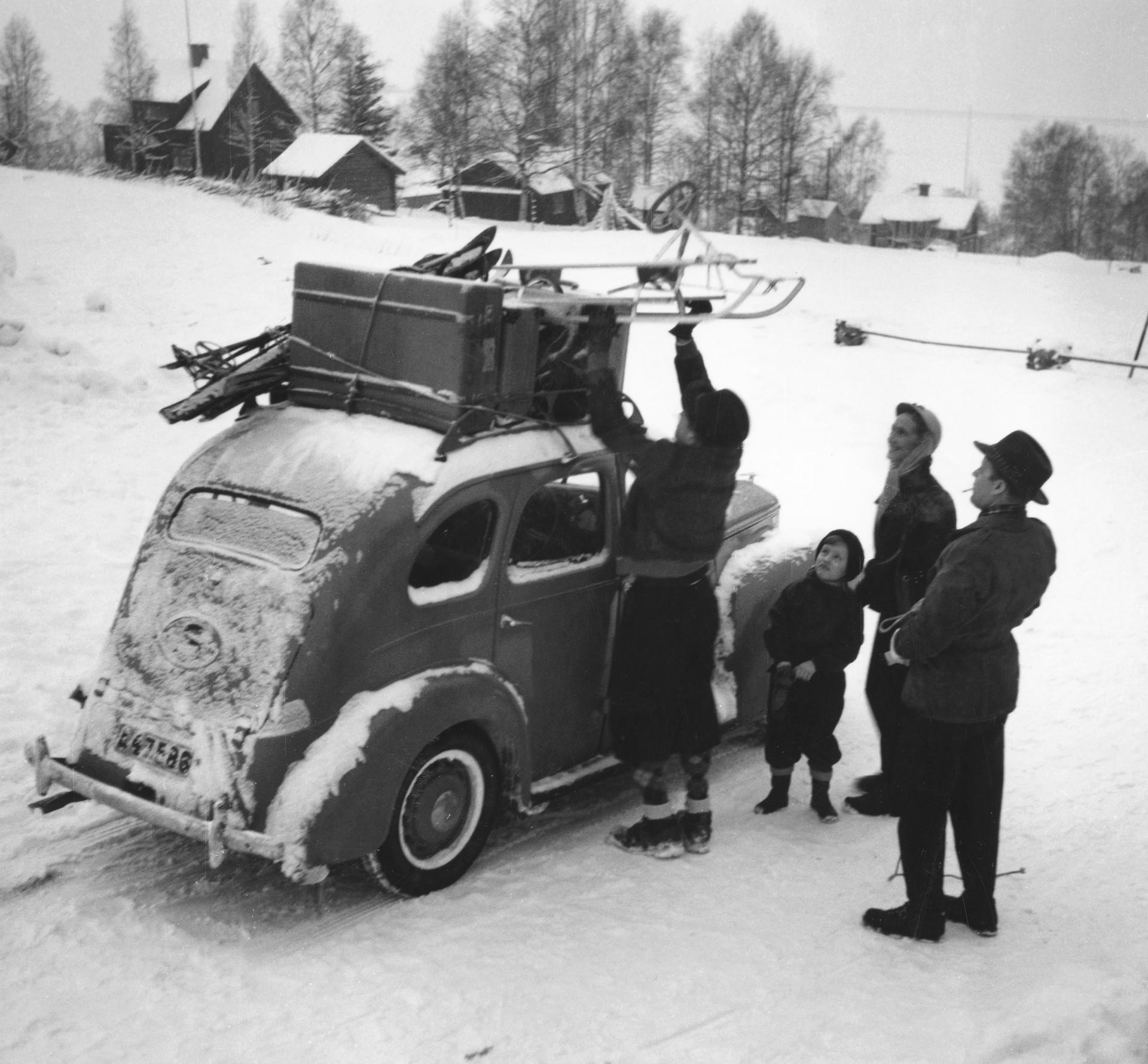 En familj lastar kälke och skidor på ett snötäckt biltak. 1953.
