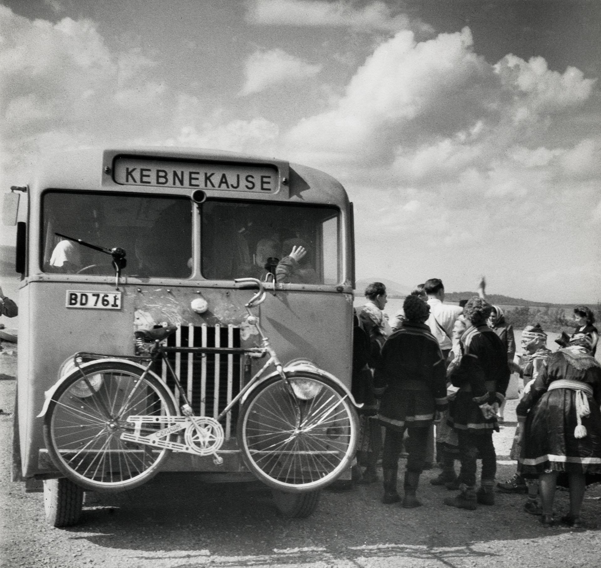 """Buss med cykel fastsatt på fronten. På skylten på bussens framsida står det """"Kebnekajse"""". Utanför bussen står en grupp människor. Holmajärvi. Juli 1946."""