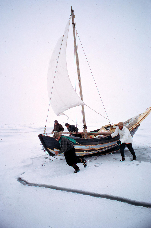 Personer som drar en liten segelbåt på snötäckt is. Säljakt, Bottenviken. 1963.