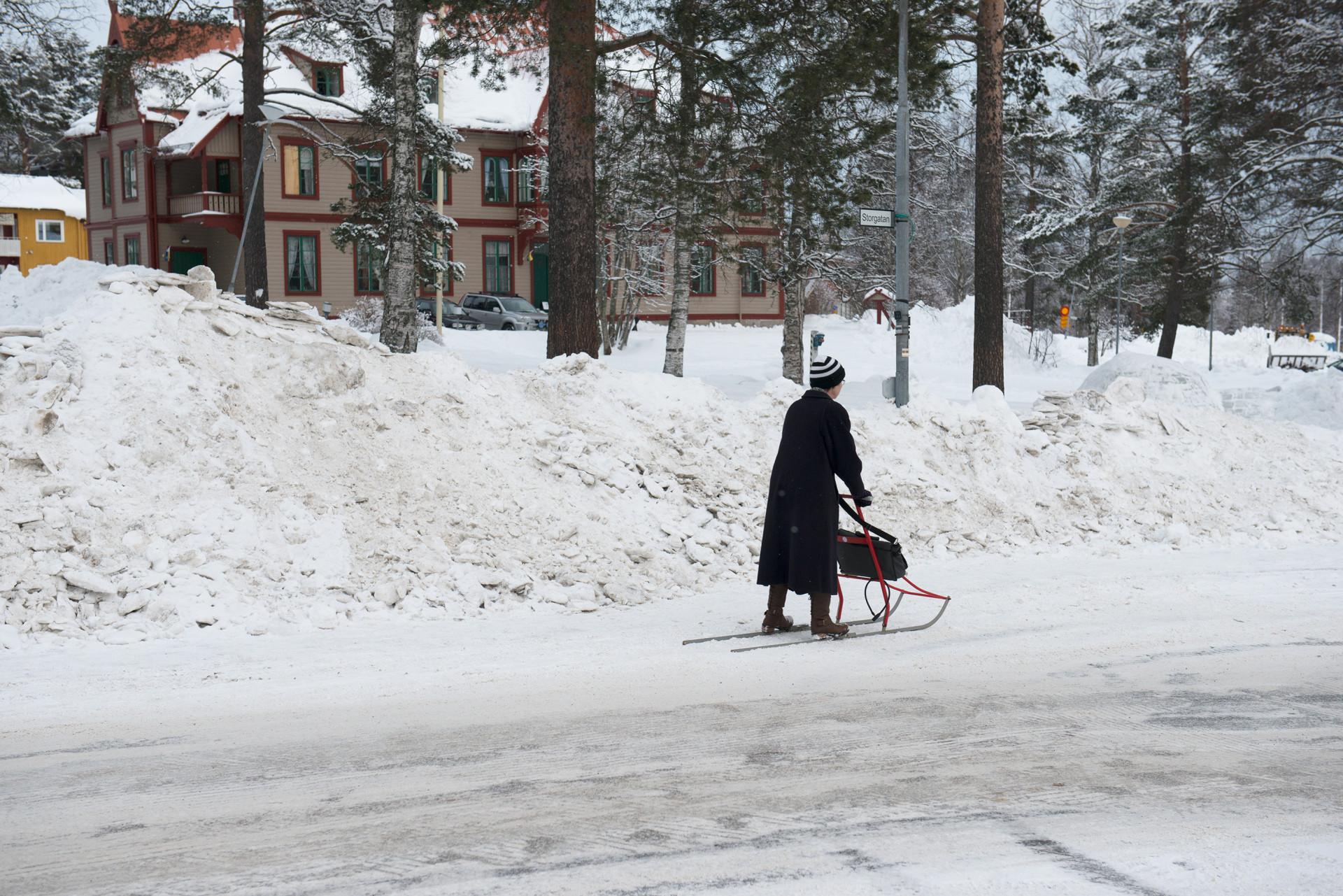 Person färdas på kälke på snötäckt gata i Vilhelmina. Februari 2014.
