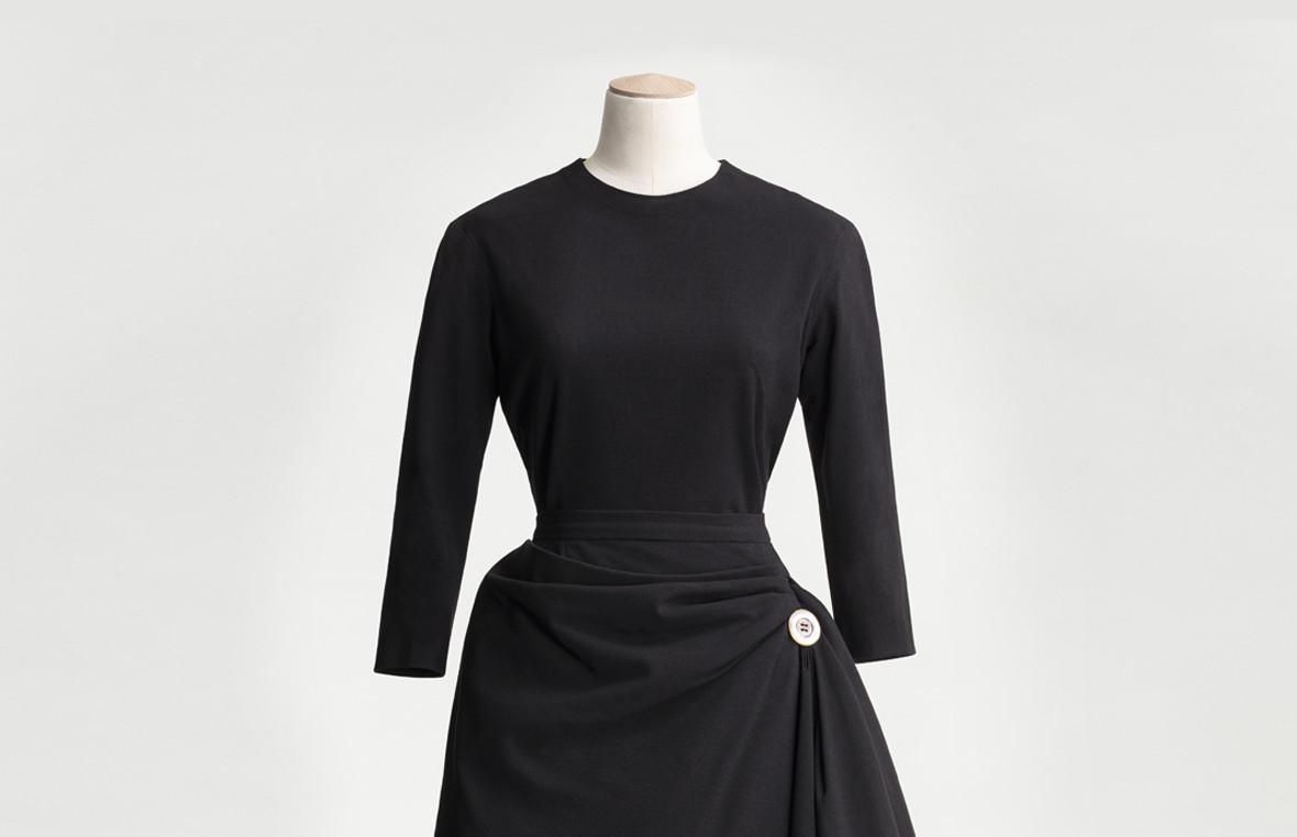 Svart klänning med draperad kjol och knapp vid höften