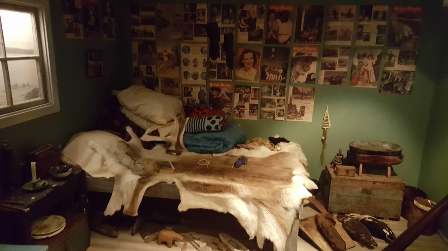 Säng med renfäll. Bilder uppsatta på väggen bakom sängen, skor står på golvet. Foto: Nordiska museet