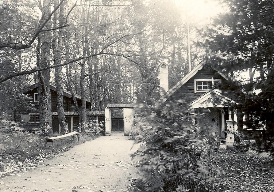 Fotografi av Smedjestugan och Davikaboden. Mellan dem syns staketet med de stora portarna. Foto: Nordiska museets arkiv.