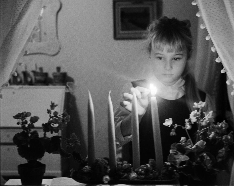 En flicka tänder det första adventsljuset. Foto: KW Gullers, 1955.