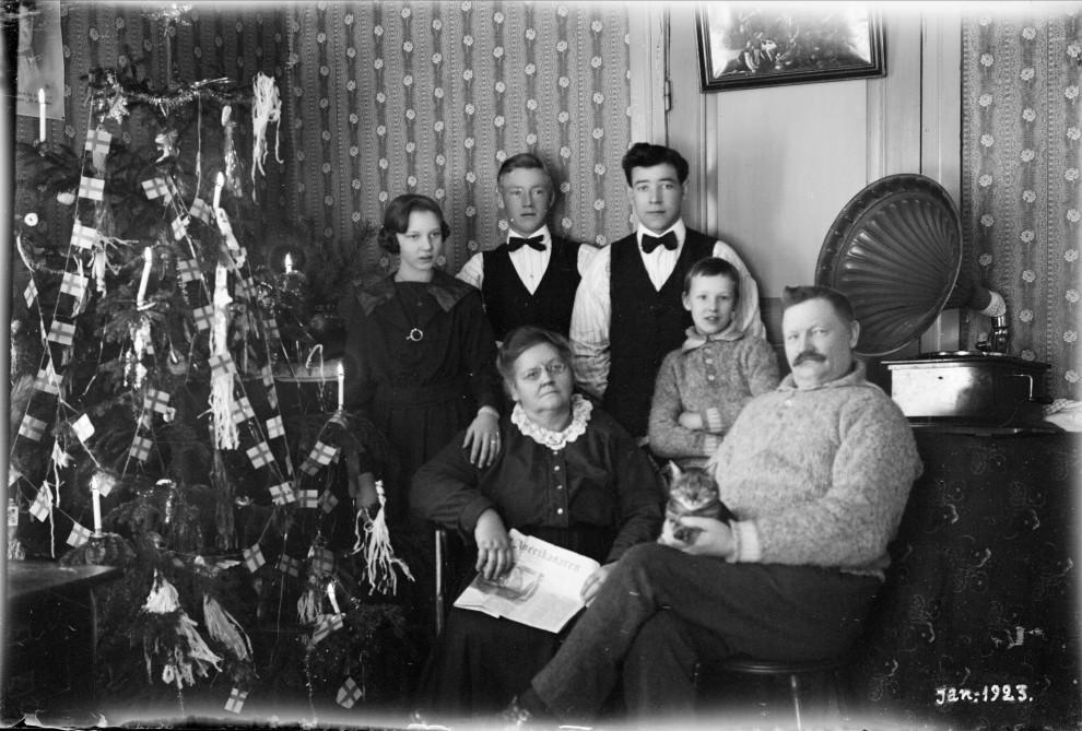 Alla familjemedlemmar, även katten, är samlade kring granen när julgransljusen tänts. Foto: Nordiska museet.