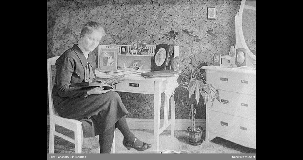 En kvinna tittar i ett fotoalbum. Lima, Dalarna. Foto: Elin Johanna Jansson, Nordiska museets arkiv. NMA.0048273