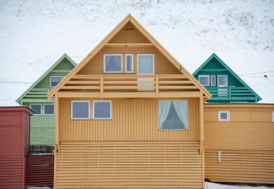 Färgglada, färgkodade hus i gult, grönt, rött och turkost. På Svalbard, Norge.