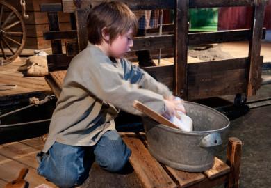 Pojke som tvättar vid floden i lekstugan