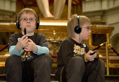 Två barn lyssnar på audioguide