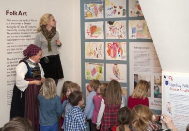 Invigning av folkkonst med skolbarn som tittar på sina teckningar i museets lokaler.