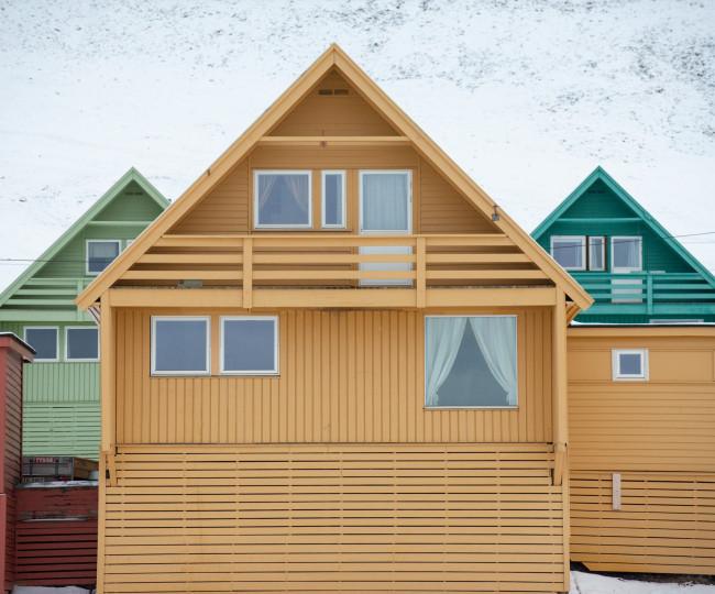 Färgglada, färgkodade trähus i gult, grönt, turkost och rött, med snö i bakgrunden. Från Longyearbyen, Svalbard.