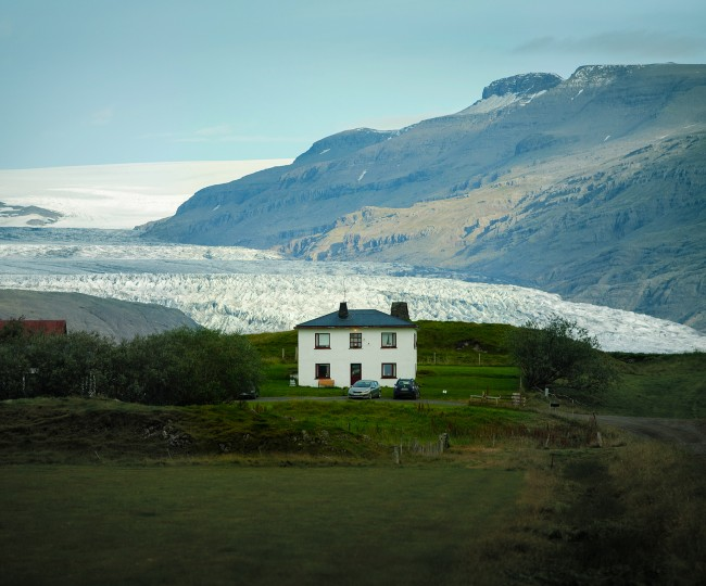 Vitt hus omgärdat av gräs och buskar. I bakgrunden en glaciär och ett berg.