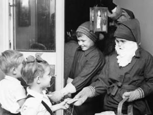Två pojkar i tomtedräkter delar ut pepparkakor till två mindre barn. Foto: Gösta Glase/ Nordiska museet