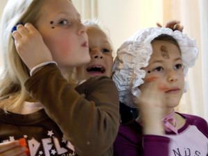 Flickor som sminkar sig i ett skapande skola-projekt.