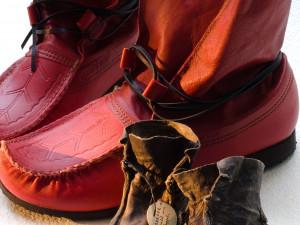 Nydesignade röda skor från 2007 bredvid äldre småbarnsskor från Koppsele i Lappland.   Den lätta renskinnsskon med sin karaktäristiska tåspets, näbb, har lång samisk tradition. Skon har länge varit uppskattad även utanför det samiska samhället. Ända sedan 1600-talet har näbbskorna utgjort en viktig samisk handelsvara. Barnens skor var kopior av de vuxnas dock med mjukare skinn, ofta sämskat renkalvskinn. Foto: Mats Landin, Nordiska museet.
