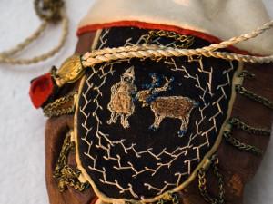 Penningpung av renskinn med svarta broderier och mässingsringar. Tillverkad av Maria Kristina Sjulsdotter, Malå socken i Lappland. Köptes av Gustaf von Düben 1868 som sedan skänkte den till Nordiska museet 1873.   Små skinnpungar för tobak, pengar eller annat smått som är lätta att bära med sig i bältet har alltid hört till den samiska utrustningen. Väskorna blev populära som turistsouvenirer redan vid 1800-talets mitt. Foto: Mats Landin, Nordiska museet.