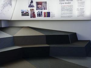 Sápmis formgivare är Codesign.  Mattan/marken täcker golvet och fortsätter upp på sittplatser och montrar. Foto: Mats Landin, Nordiska museet.