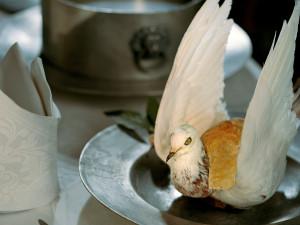 """En elegant anrättad duva ligger på en tallrik av tenn. Besticken har skaft av silver och emalj - endast de mycket förmögna kunde förse sina gäster med både kniv och gaffel. Duvkött ansågs lämplig mat för flegmatiker och melankoliker som behövde något """"hetsande"""" för att balansera sitt temperament. Foto: Mats Landin, Nordiska museet."""