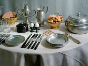 Frukosten är serverad på ett sidobord i den borgerliga stads- våningen. På skänken (ej på bild) står ett fat med stekt sill och kokt potatis. Sillen har sedan medeltiden varit vardagsföda, men potatisen slog igenom som basmat först i mitten av 1800-talet. Den gamla finservisen av tenn används nu till vardags. Ur terrinen serveras gröt och i tillbringaren finns mjölk eller vatten med sirap (s.k. grötväta). Efter maten dracks det kaffe. Foto: Mats Landin, Nordiska museet.