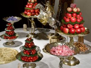Konfektbordet med den förgyllda tårtan är festens praktfulla final. På vackra silverfat och i skålar finns marsipanfigurer, kanderade blommor, frukter som plommon, körsbär och äpplen, hasselnötter, kastanjer och brända mandlar. En närmare titt på sötsakerna, som kom från sockerbagare i de större städerna, avslöjar bibliska motiv och figurer, gärna överdragna med guld. Våra dagars jultomtar och påskkycklingar i choklad och marsipan är ett arv från dessa figurer. Foto: Mats Landin, Nordiska museet.