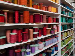 Garn som använts i olika produktioner bildar en vägg av färg i en av vävsalarna. Rester från olika vävnader sorteras efter färg och fungerar som en färgpalett där garn väljs. Foto: Peter Segemark, Nordiska museet.