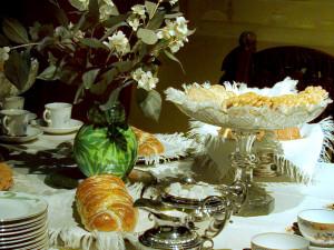 Man har släppt in solen, ljuset och naturen i hemmet. Vilda blommor pryder kaffebordet. Sju sorters kakor, vetebröd och sockerkaka är framsatta. Tack vare järnspisen med bakugn, jästpulvret, pressjästen och det inhemskt odlade vetet, kan husmor baka en helt annan sorts bröd än tidigare. Kaffekalas blir ett omtyckt nöje. Kanske någon saknar gräddtårtan? Inte förrän på 1920-talet kommer den på kaffebordet, den tillhörde länge en av festmiddagens många rätter. Foto: Mats Landin, Nordiska museet.