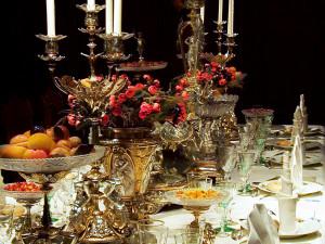 Den pampiga dukningen med brutna servetter har släktskap med 1600-talet. Fortfarande är måltiden indelad i tre avdelningar, två från köket och en från konditorn. Maträtterna står inte längre på bordet. Betjäningen serverar rätterna från köket varefter de ska ätas. Vid varje kuvert finns en matsedel på franska där gästerna kan se vad som bjuds. Konfekten, en del av desserten, står framme på bordet som dekoration under hela måltiden. Foto: Mats Landin, Nordiska museet.